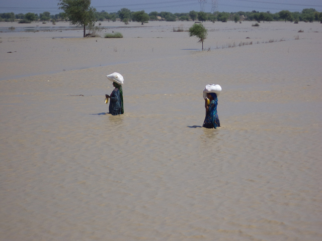 Two Pakistani women carry loads while wading through floodwaters, 13 September 2012. muslimhandsuk / flickr