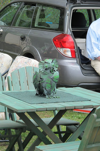 The green owl on the wooden deck set seems as if it were arranged already on someone's porch.