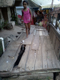 A little girl crosses a makeshift bridge in a favela in Rio de Janeiro. Read the linked blog posts to see how DIY aerial photography projects helped find, and accelerate the replacement of, this neighborhood vulnerability.