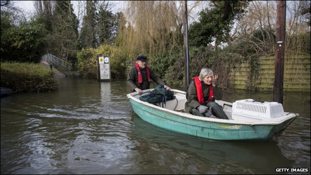An man pushes a boat carrying his wife and their pet through floodwaters in Britain, 12 February 2014. The swollen River Thames caused major flooding after the UK's wettest January since 1766. Photo: Getty Images / BBC News