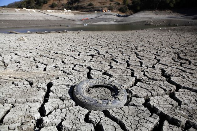A discarded tire is seen stuck in the exposed lake bed of the Almaden Reservoir which is experiencing extremely low water levels due to the ongoing drought, in San Jose, 30 January 2014. Photo: Michael Short / The Chronicle