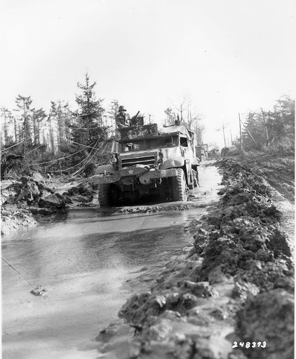 Battle of Hürtgen Forest: A 1st Infantry Division half-track plows its way through a muddy road in the Hurtgen Forest. 16th Infantry Regiment, 1st Infantry Division. 15 Feb 1945.