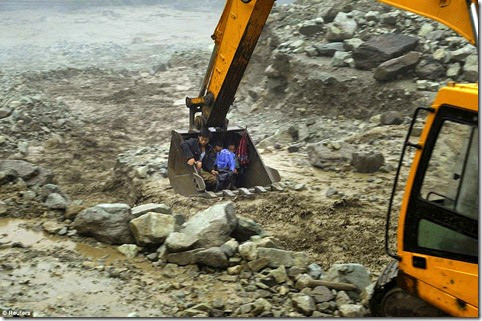 An excavator is used to move villagers away from a flooded area during heavy rainfall in Yingxiu, Wenchuan county, Sichuan province, China, July 10