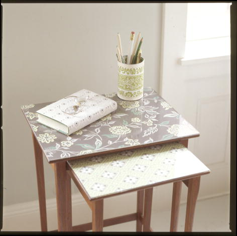 Covering an old table with wallpaper is a great way to disguise scratches. (marthastewart.com)
