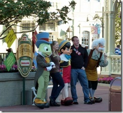 Disney characters pose with a young couple
