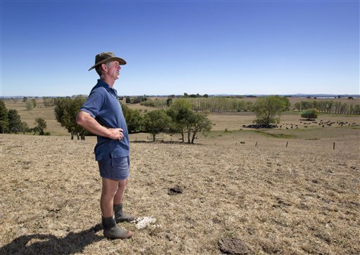 In this photo taken on 11 March 2013, farmer Peter Brown walks on the dry ground at his dairy farm near Ohinewai, New Zealand. A drought in New Zealand's North Island is costing farmers millions of dollars each day and is beginning to take a toll on the country's economy. Photo: Brett Phibbs / New Zealand Herald / AP Photo