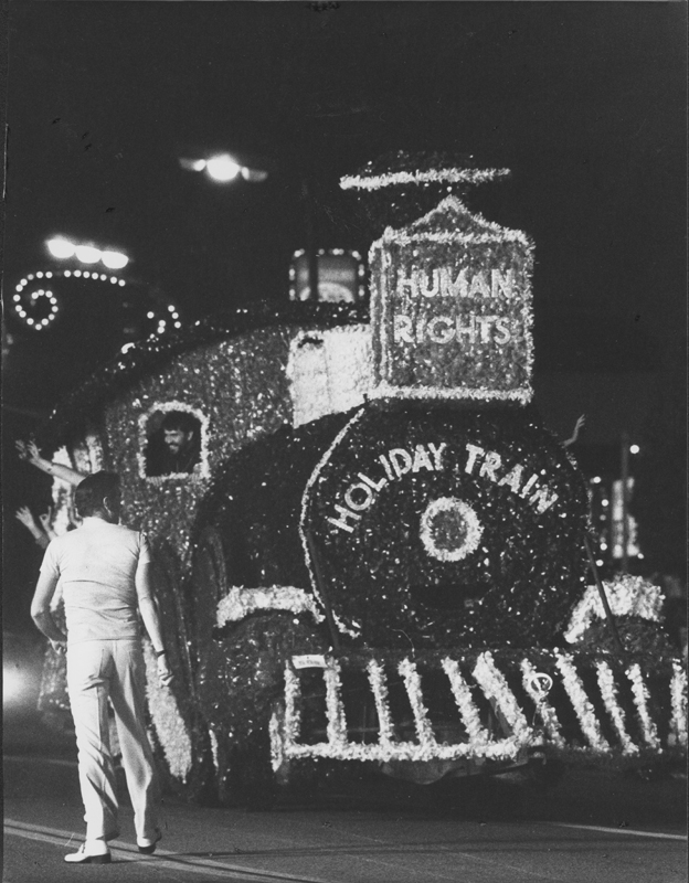 The Human Rights Train becomes the first float sponsored by an LGBT organization in the Hollywood Santa Claus Lane Parade. Pat Rocco with back to camera and Reverend Troy Perry is visible in the train window. November 1977.