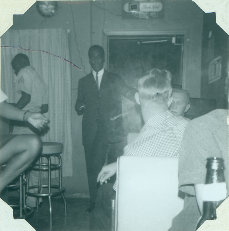 "Patrons gather at Mary Ellen's Top Hat. The man standing in the center is identified as ""Mr. Elegance"" and the man sitting (right) facing the camera as Charles. Spring 1963."