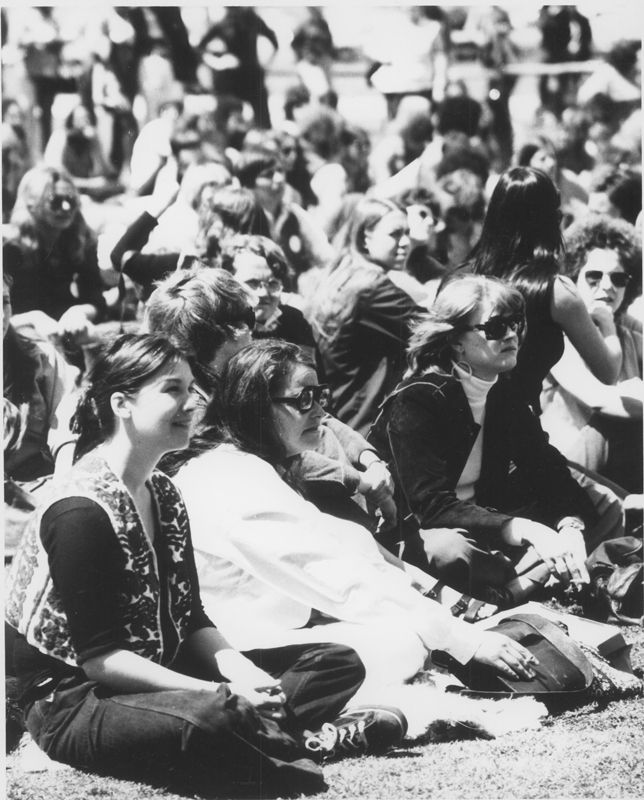 Kate Millet sits on the grass (2nd from left) with Zoe Budapest (braided vest), high priestess of Susan B. Anthony Coven #1 of Feminist Wicca, at the first National Lesbian Conference, UCLA. April 14, 1973.