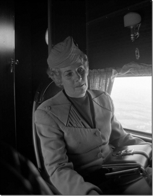 Flight attendant in a 1929 TAT stewardess uniform aboard a Ford Tri-Motor in the livery of Transcontinental Air Transport, the forerunner of Trans World Airlines, as it would have appeared at the inauguration of TWA's transcontinental passenger service in 1929. This aircraft toured the U.S. for the 45th anniversary of TWA's transcontinental service in 1974. The plane is now housed at the McMinnville, Ore., airport and flies at airshows. This photo was made at Weir Cook (now Indianapolis International) Airport.