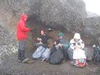 Lunch in the shelter of a rock to protect us from the blowing rain. Steven, Simina, Matt, Maggie.