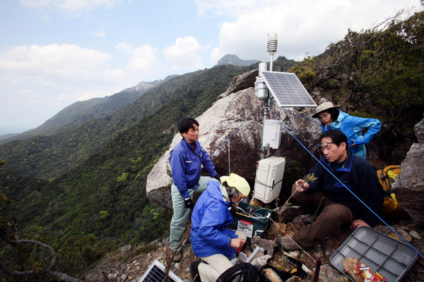 Osamu Nagafuchi, second right, an environmental engineer, checks a monitoring station around Yakushima to measure levels in the air of ozone and sulfur emissions, which are typically the byproducts of burned coal or automobile exhaust. Mr. Nagafuchi believes air pollution from China is killing endangered trees in Japan. Photo: Kosuke Okahara / The New York Times