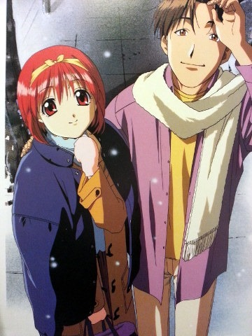 Akari and Hiroyuki standing together on the sidewalk in winter clothes smiling up at the viewer as snow falls