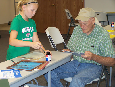 Highlanders 4-H member Kiley Wood, daughter of Brian and Angie Wood, worked with her grandpa Dean Schoon to create several pieces of art at the 4-H Photo Mounting Day.  Photo courtesy:  Washington County Extension.