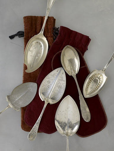 Large late-19th-century serving utensils, used for pies and pastries, are ornately decorated and come in a variety of imaginative shapes, including a helmet, far right.