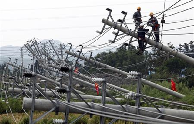 Labourers work to repair downed power lines after pylons were toppled by Typhoon Haikui in Wenling, Zhejiang province on 8 August 2012. REUTERS / China Daily