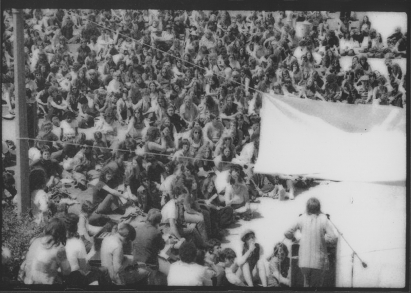 Thousands listen to Robin Morgan give the keynote address from Janss Steps at the first National Lesbian Conference, UCLA. April 14, 1973.