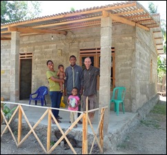 Sinta with her husband Apoli and 2 neices proudly standing outside their newly finished home.