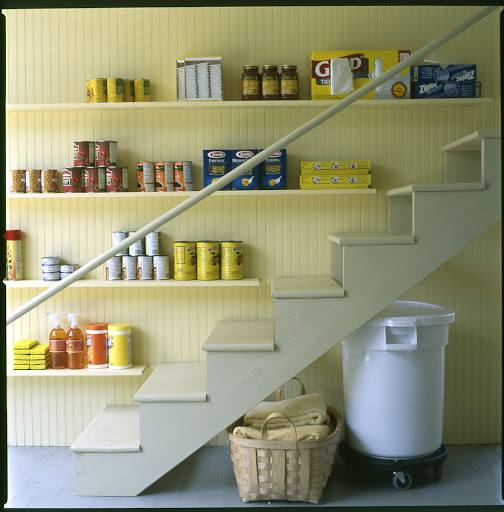 Narrow shelving installed along a stairway, like one leading to the basement, is perfect for storing cleaning products, trash bags, or other non-perishable goods.