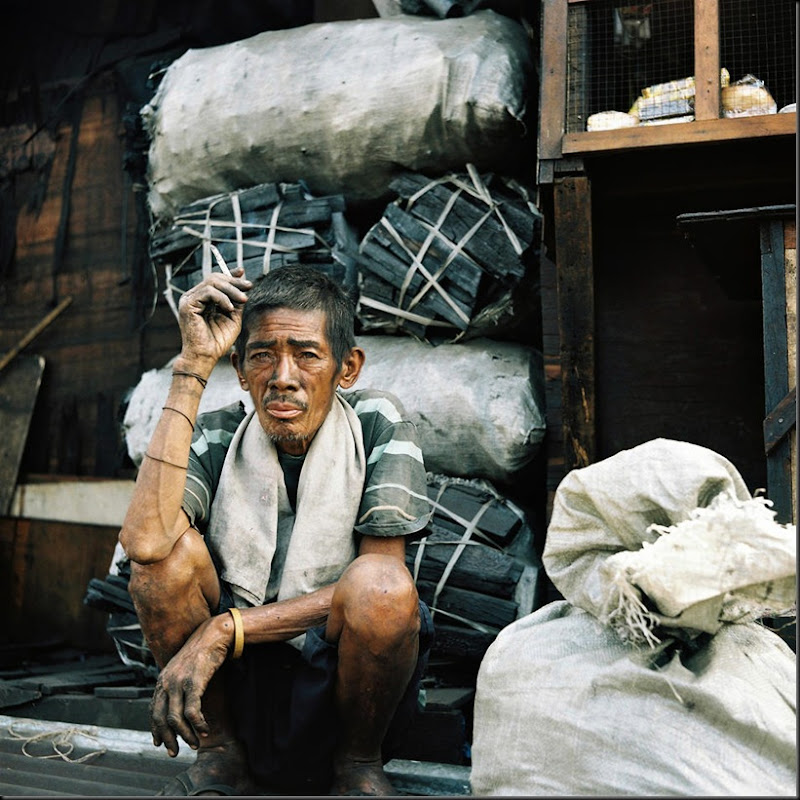 A charcoal maker rests for a cigarette break inside one of the kilns producing charcoal in Happyland, a large garbage dump in Manila. Most of the residents of Happyland collect recyclable materials such as plastics, bottles, and metal parts where they exchange them at nearby junk shops. They also salvage any wood from the dump and nearby construction sites for the charcoal makers to produce charcoal from. Scavengers earn a measly eighty pesos (USD 2.00) for a day's work while the charcoal makers are better off with two hundred pesos (USD 5.00).