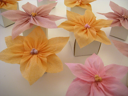Glue flowers to the top of small favor boxes. We used two different sizes to create variation in height.