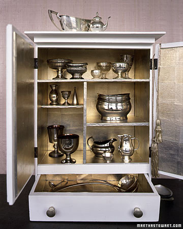 An exquisite silver leafed cabinet makes a beautiful backdrop for a silver collection. (marthastewart.com)
