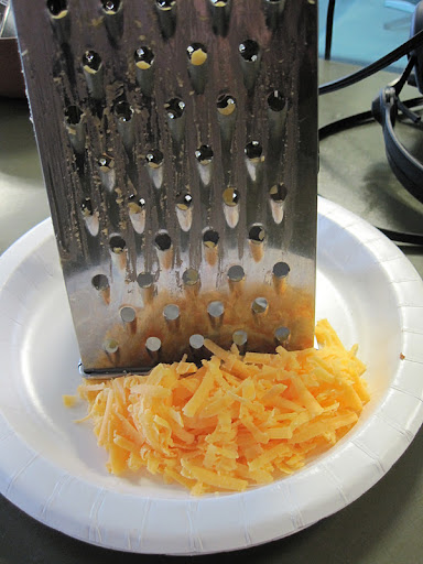 Grating cheddar cheese.