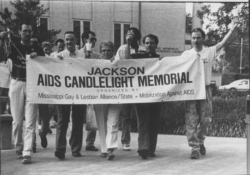 Edgar Sandifer with members of the Mississippi Gay & Lesbian Alliance and Mobilization against AIDS marching with a banner promoting the AIDS Candlelight Memorial. May 28, 1989.
