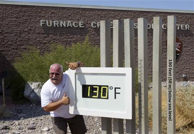 Craig Blanchard, a Park Service employee, poses in front of an unofficial temperature gauge at the Furnace Creek Visitor Center in Death Valley National Park in California 29 June 2013. Photo: Steve Marcus / REUTERS