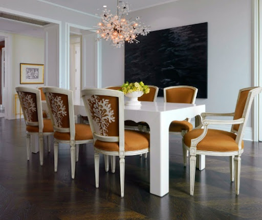 A set of caramel dining chairs surround a glossy white table. (cocokelley.blogspot.com)