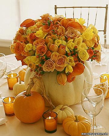 A white-pumpkin shell becomes the vase for an arrangement of roses, daffodils, ranunculuses, calla lilies, tulips, and hypericum berries in fall colors.