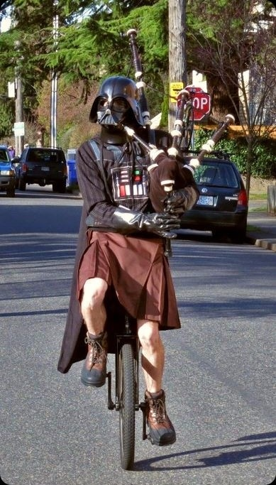 a person in a Darth Vader mask and cape, and a kilt, riding a unicycle, playing Star Wars music on a bagpipe