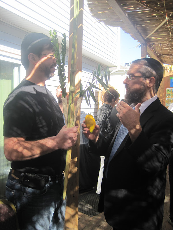 Rabbi Travitsky shaking a lulav with Dwain Eichenbaum