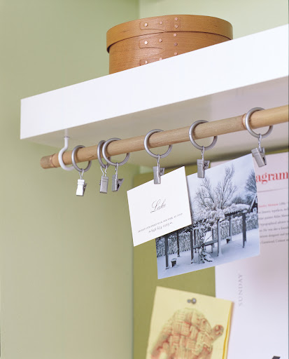 Here, cup hooks and a drapery rod function as a place to display photos and business cards.
