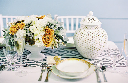 Blanc de Chine vases along with gorgeous gold-trimmed fine china, silver utensils, and a chain-link table runner helped create a beautiful tablescape.