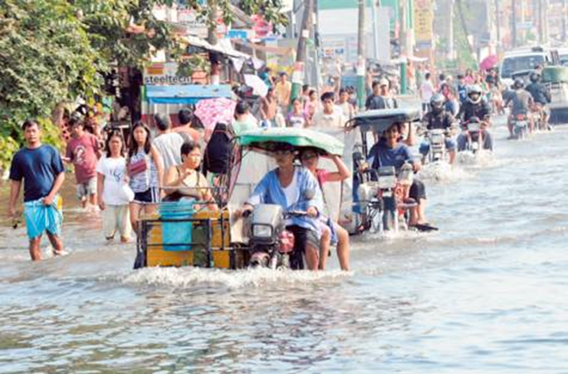 Residents commute along a flooded stretch of road in Calumpit town, north of Manila, 10 August 2012. Thousands more flood victims crammed into evacuation centres on Friday as waist-high water covered vast farming regions and the death toll rose to 60. AFP