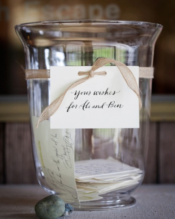 A large hurricane vase is displayed with stacks of rubber-stamped cards for guests to write on. Stones from a nearby beach weigh down the cards.