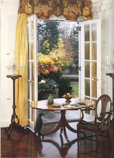 I love how the colors of this window treatment and the mahogany, satinwood and tulipwood pieces that decorate this breakfast nook perfectly complement the fall foliage.