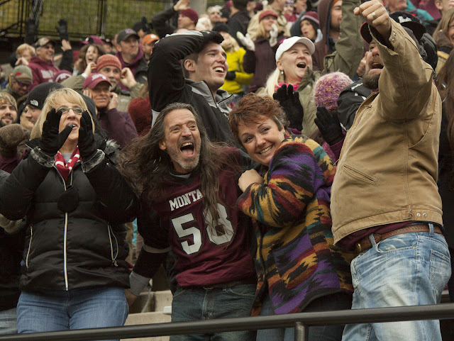 Griz fans Bunny Saylor (l), Marko Wagenmann, Kindra Evans, and Brian Evans cheer on their hometown Griz after redshirt junior linebacker Jordan Tripp stripped, recovered, and scored an 80-yard fumble.  Washington-Grizzly Stadium in Missoula, Mont., October 27th, 2012.
