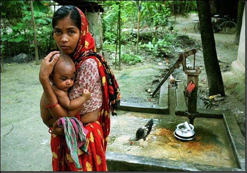 BANGLADESH. Khulna. Jessore. Jhikargachha village. A woman whose arms and sides show the telltale black marks of arsenic poisoning has only this pump for fresh water.2000.