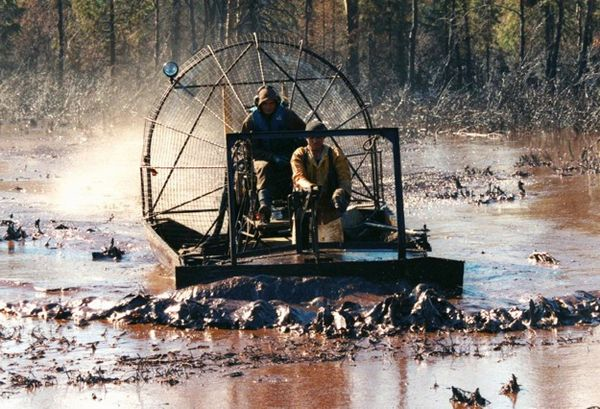 Russian workers riding an airboat clean up an oil slick in the river Kolva near the Russian town of Usinsk in this 16 August 1995 file photo. Gennady Galperin / REUTERS