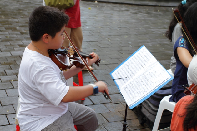 Kid learning to play the violin at Taman Suropati, Jakarta, Indonesia