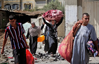 Palestinians carry belongings as they walk on the rubble of houses destroyed by Israeli strikes in Beit Hanoun, northern Gaza Strip, Saturday, July 26, 2014. Thousands of Gaza residents who had fled Israel-Hamas fighting streamed back to devastated border areas during a lull Saturday, and were met by large-scale destruction: scores of homes were pulverized, wreckage blocked roads and power cables dangled in the streets. (AP Photo/Lefteris Pitarakis)