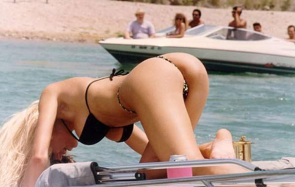 Image of bikini-clad woman with boat in the background