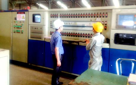 Anh Phạm Bá Long (trái) hướng dẫn công nhân thực hiện quy trình sấy - nung tại phân xưởng.