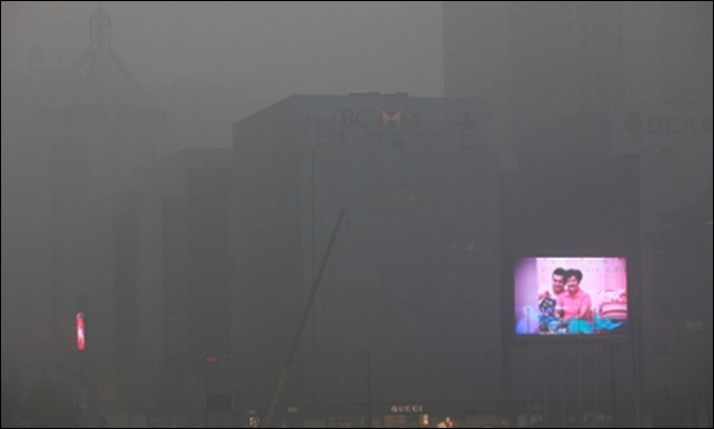 A big screen flashes commercials on the exterior of an office building in Xi'an in north-west China as the air quality index reaches 282 due to pollution. Photo Mayi Wong / EPA