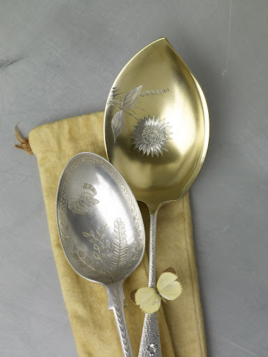 These late-Victorian spoons are embellished with intricate butterflies and flowers; the larger one is washed with a thin layer of gold.