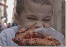 Un bambino mangia una pizza