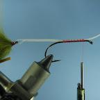 Dla uchronienia palców przed nieprzyjemnymi skaleczeniami podczas dalszej pracy zakładamy teraz na grot haka tylnej muszki odcinek rurki plastikowej. Przykładamy teraz łącznik do trzonka przedniego haka i przywiązujemy do nici wiodącej.