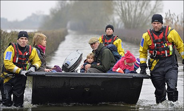 A boat steered by emergency services personnel carries residents along a flooded road from the village of Muchelney on the Somerset Levels. Photo: Toby Melville / REUTERS